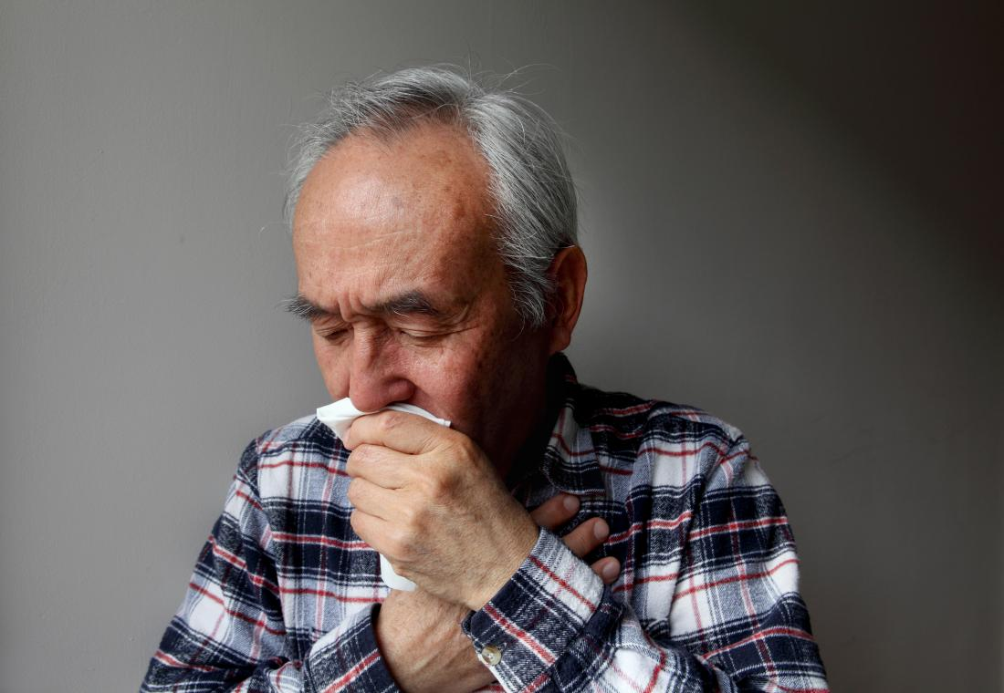 Senior man with rheumatoid arthritis coughing into a tissue because of pulmonary fibrosis.