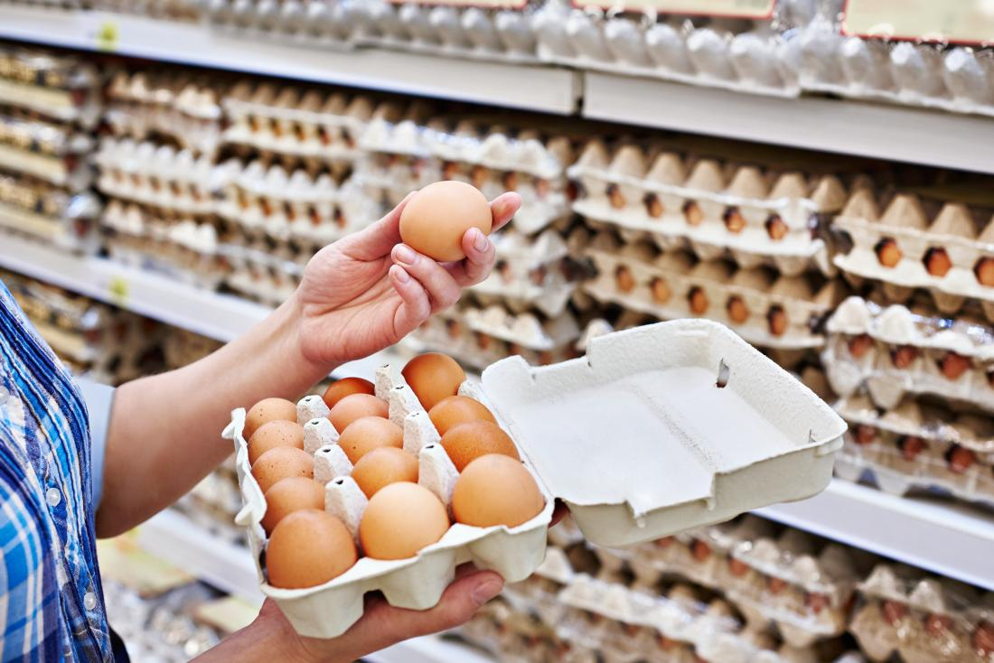Woman holding eggs in a supermarket