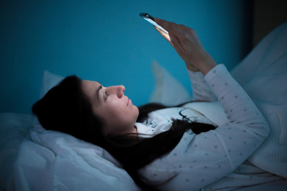 woman in bed staying up late looking at smart phone