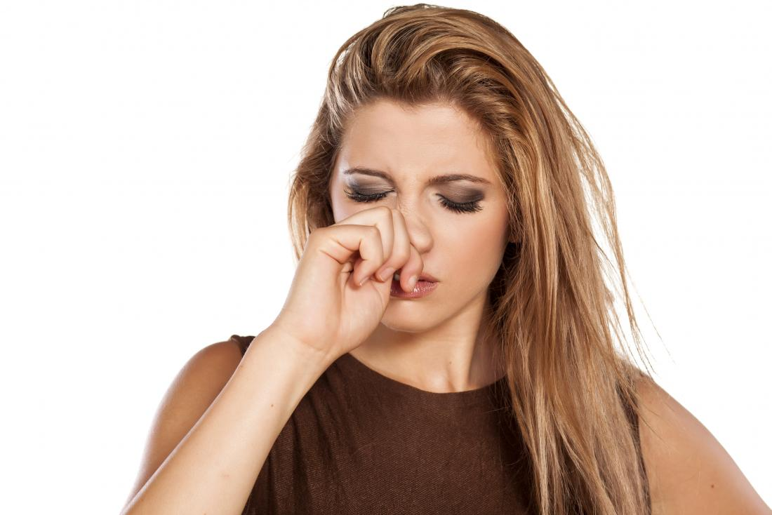 woman pressing the side of her nose