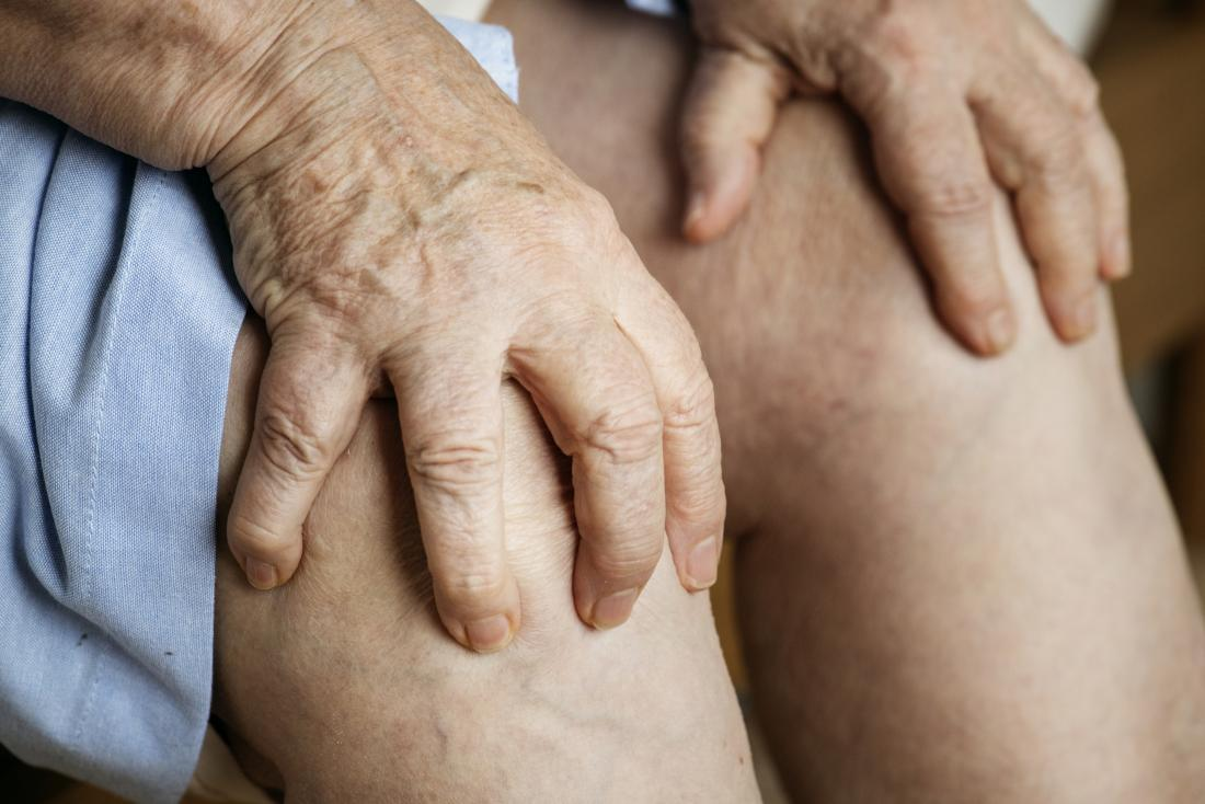 Senior person hands holding knees representing difference between gout and arthritis