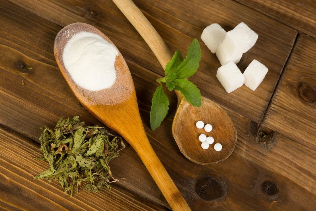 Sugar and sweeteners on wooden table and wooden spoons with leaves