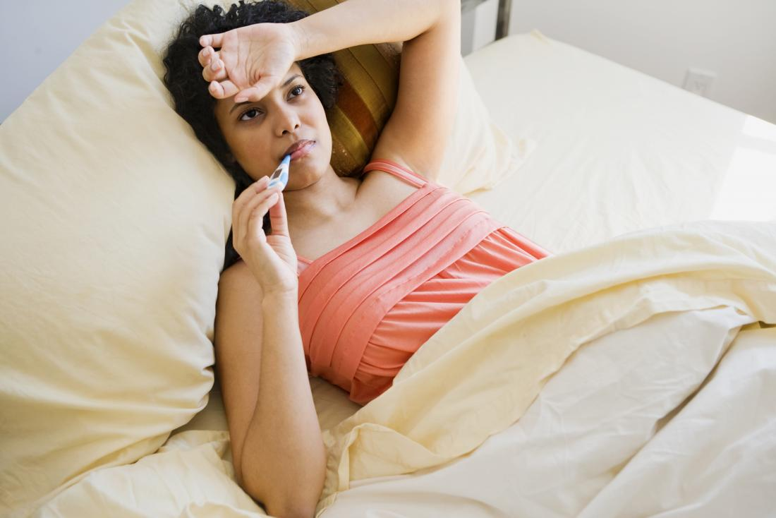 Woman with a fever measuring her temperature in bed