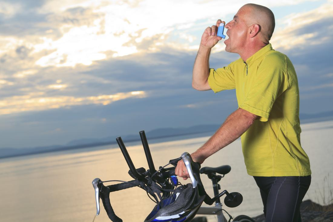 Man using an asthma inhaler whilst holding his bike