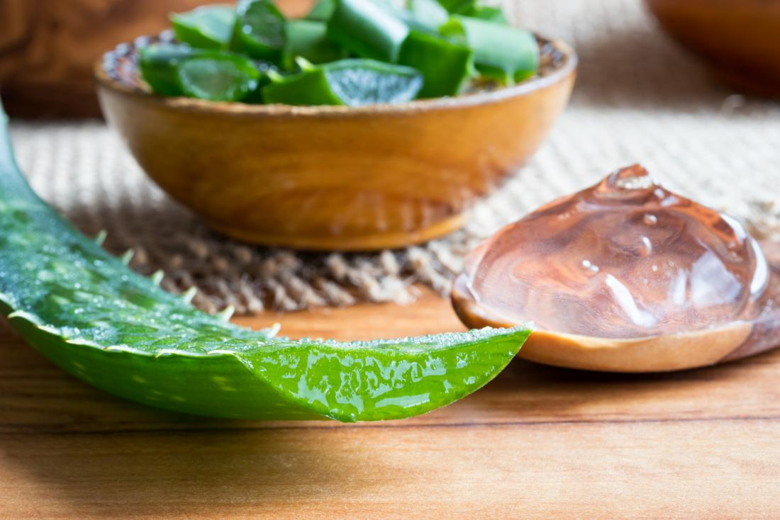 Aloe vera plant and gel on wooden spoon and in bowl on tabletop
