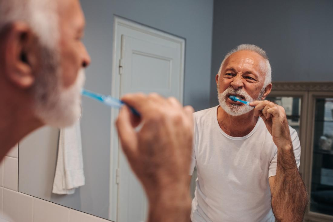 Senior man brushing teeth in front of bathroom mirror.