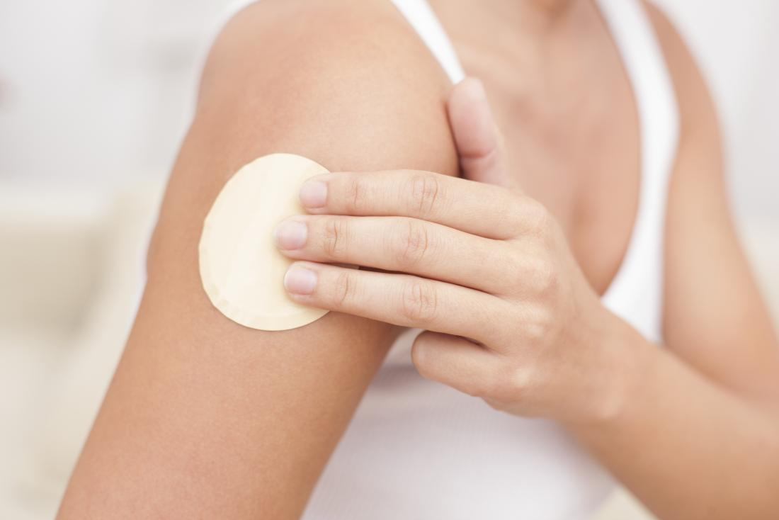 Woman putting nicotine patch on arm