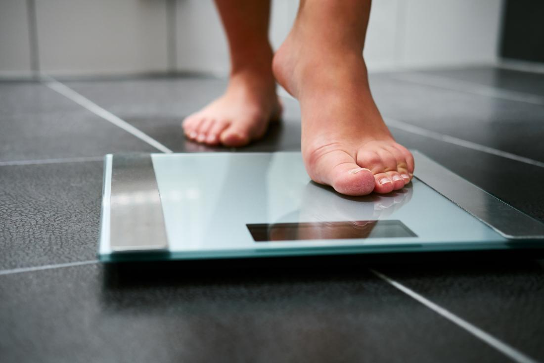 Person stepping on weighing scales