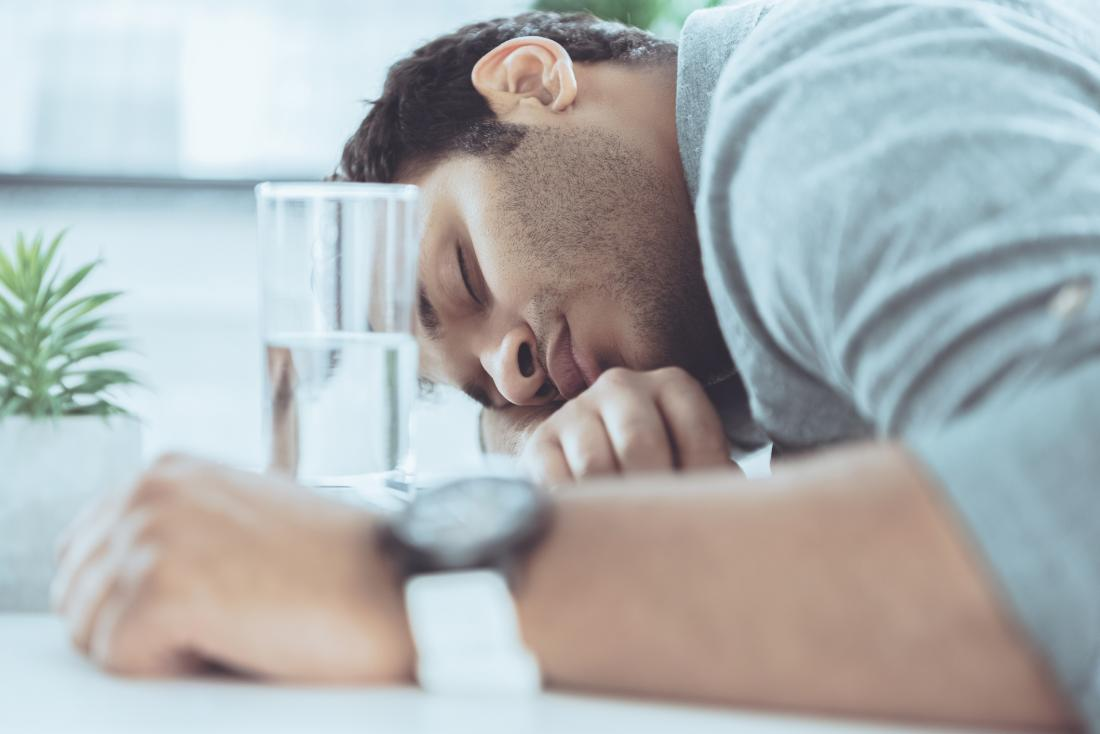 man sleeping on table with glass of water