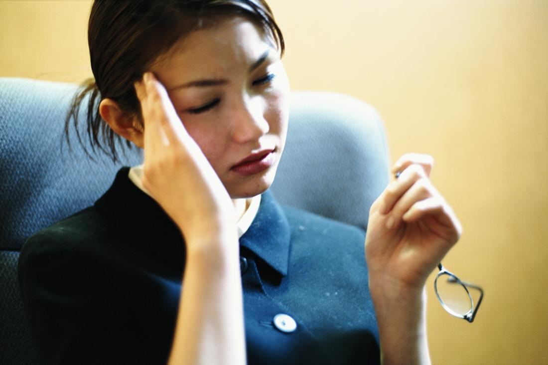 Woman with headache and dizziness holding side of head in pain