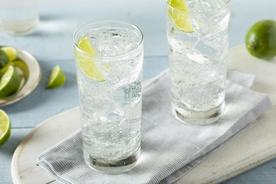 Fizzy tonic water in tall glasses with lime slices