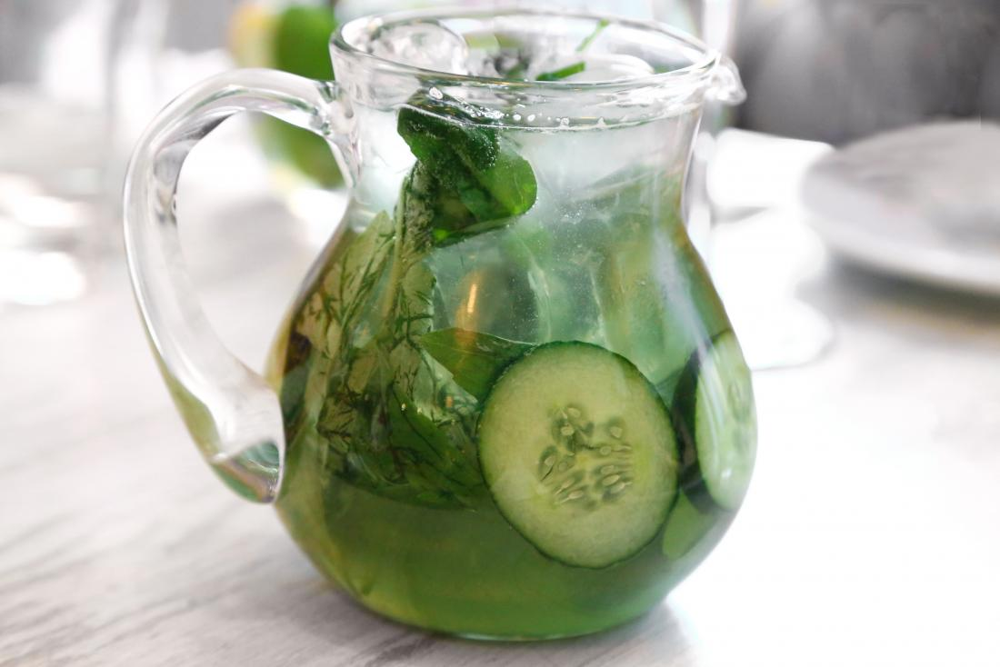 Cucumber water with basil, mint and other herbs in jug