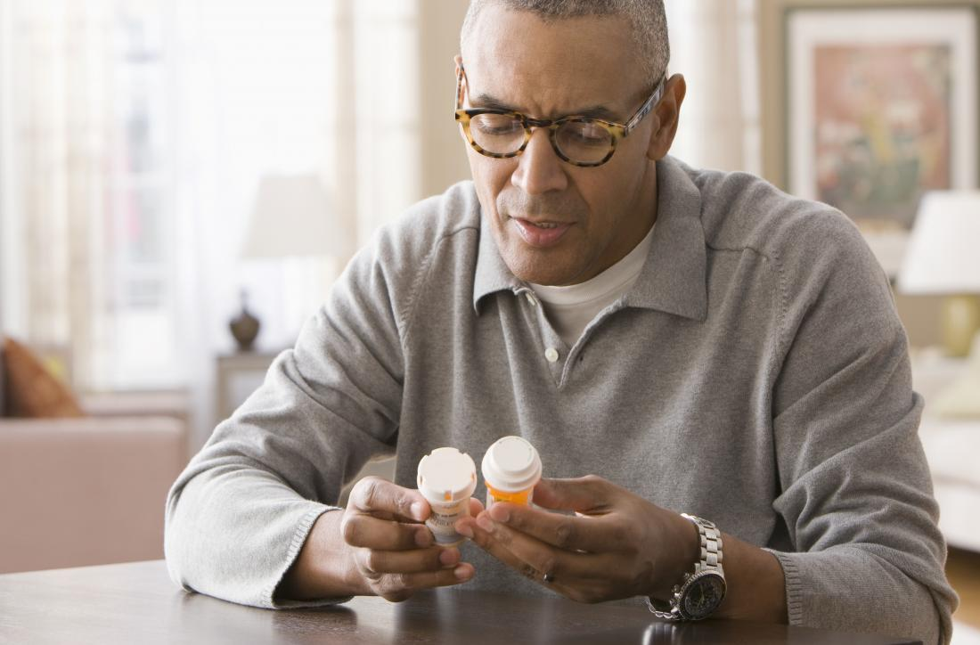Man looking at pill bottles in home.