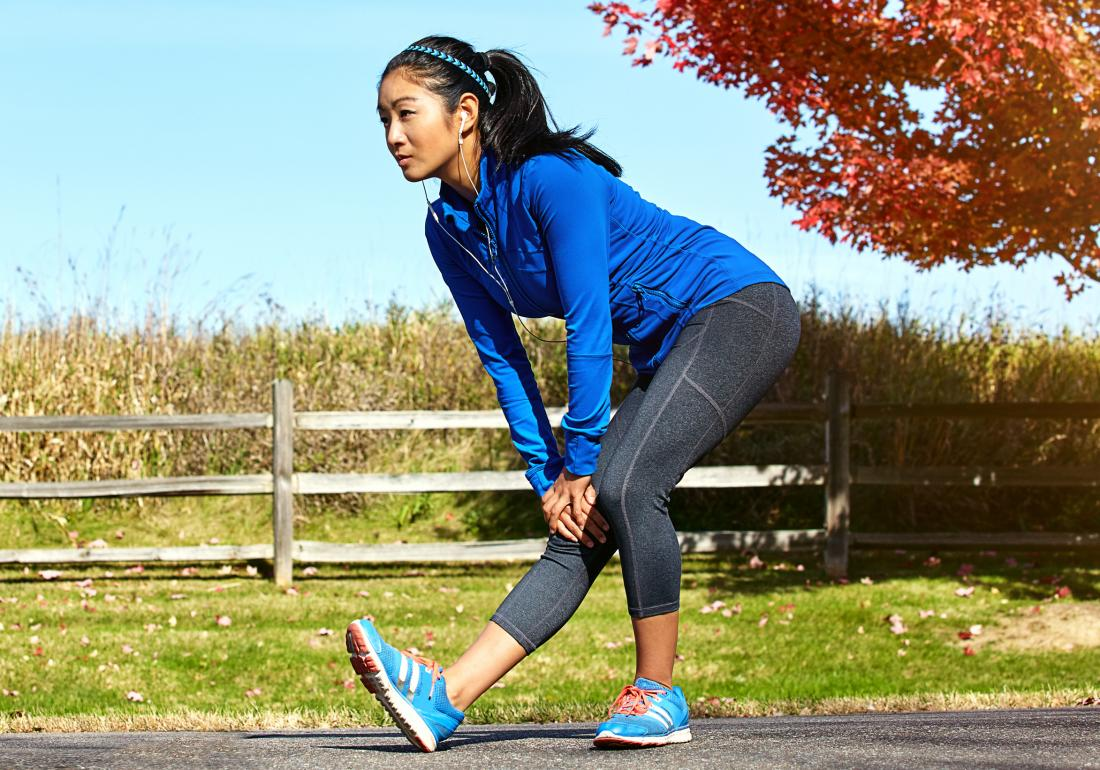 Woman outdoors doing standing hamstring stretch