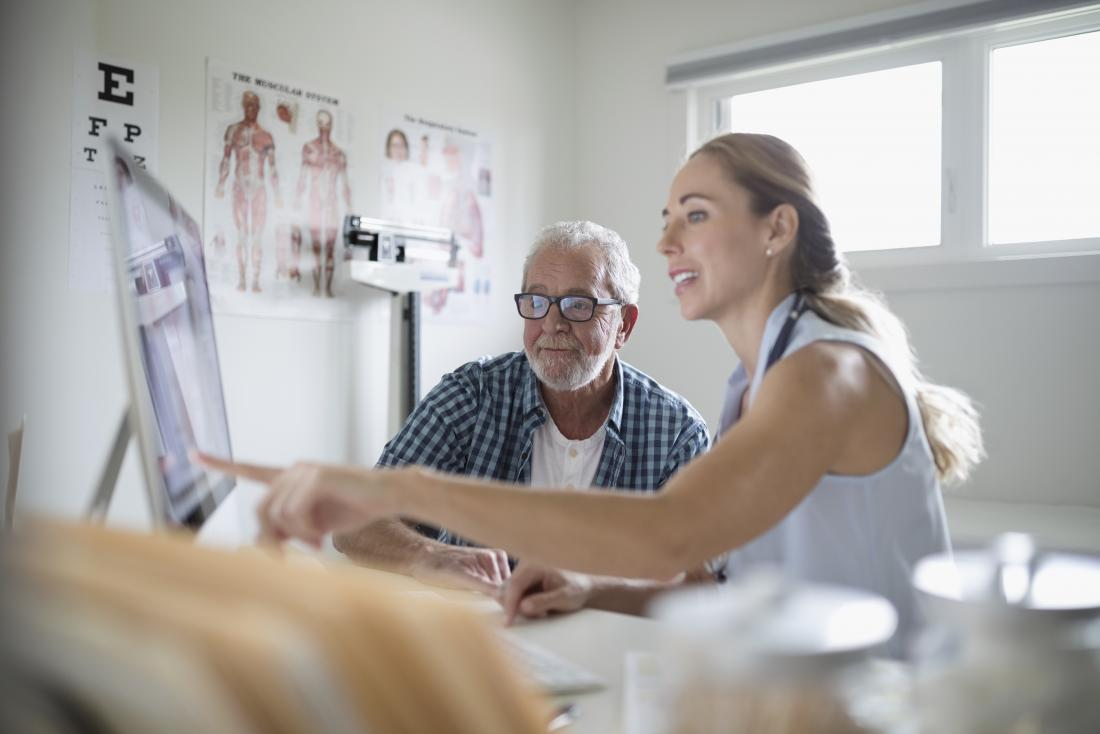 Female doctor with senior male patient in office looking at computer screen