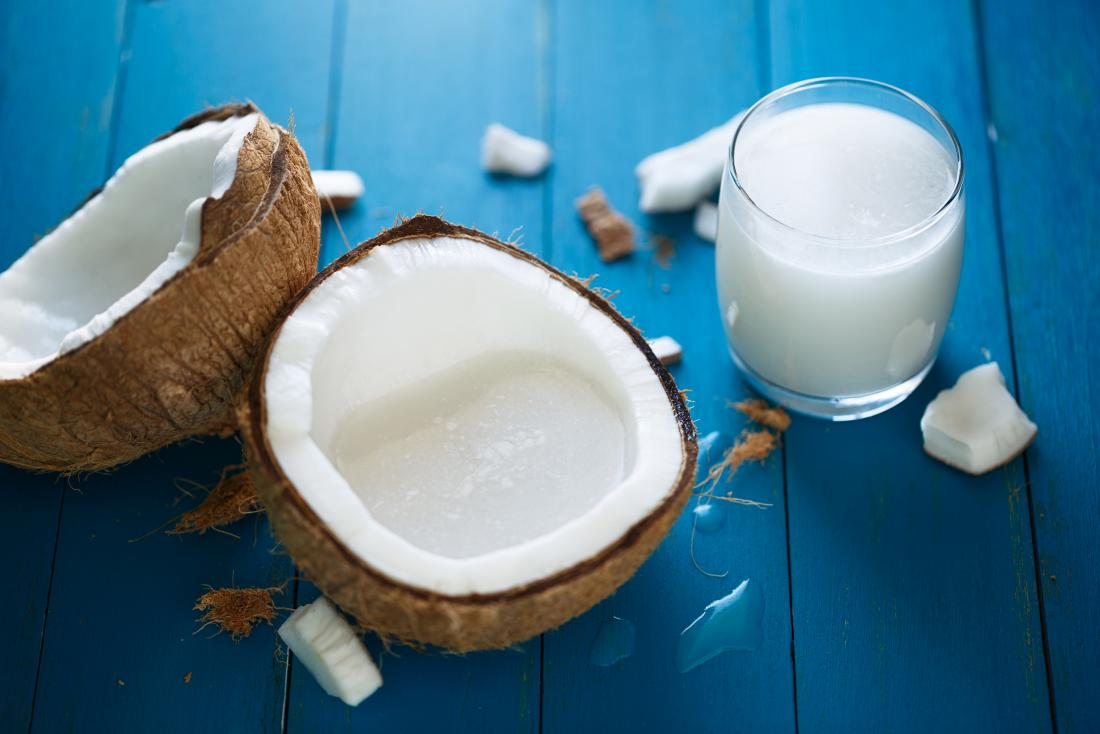 Halved coconut on blue wooden tabletop with glass of coconut milk