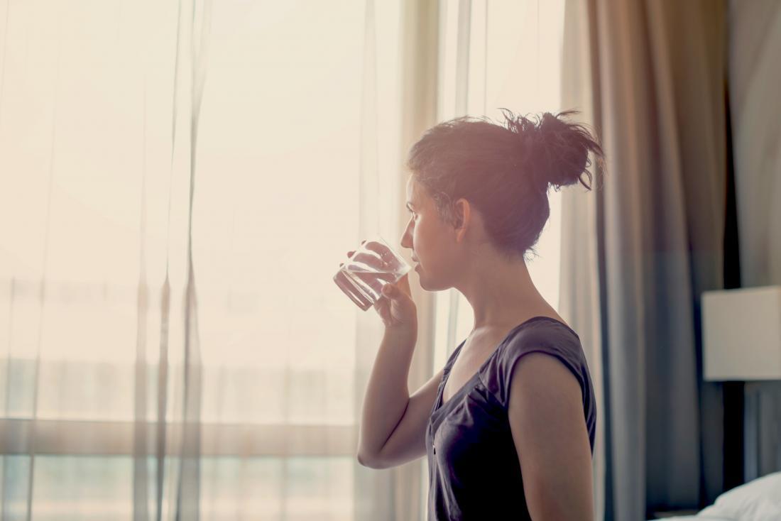 Mujer agua potable como parte de la limpieza natural del colon