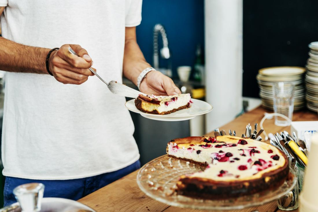 Man taking slice of cake onto plate in kitchen