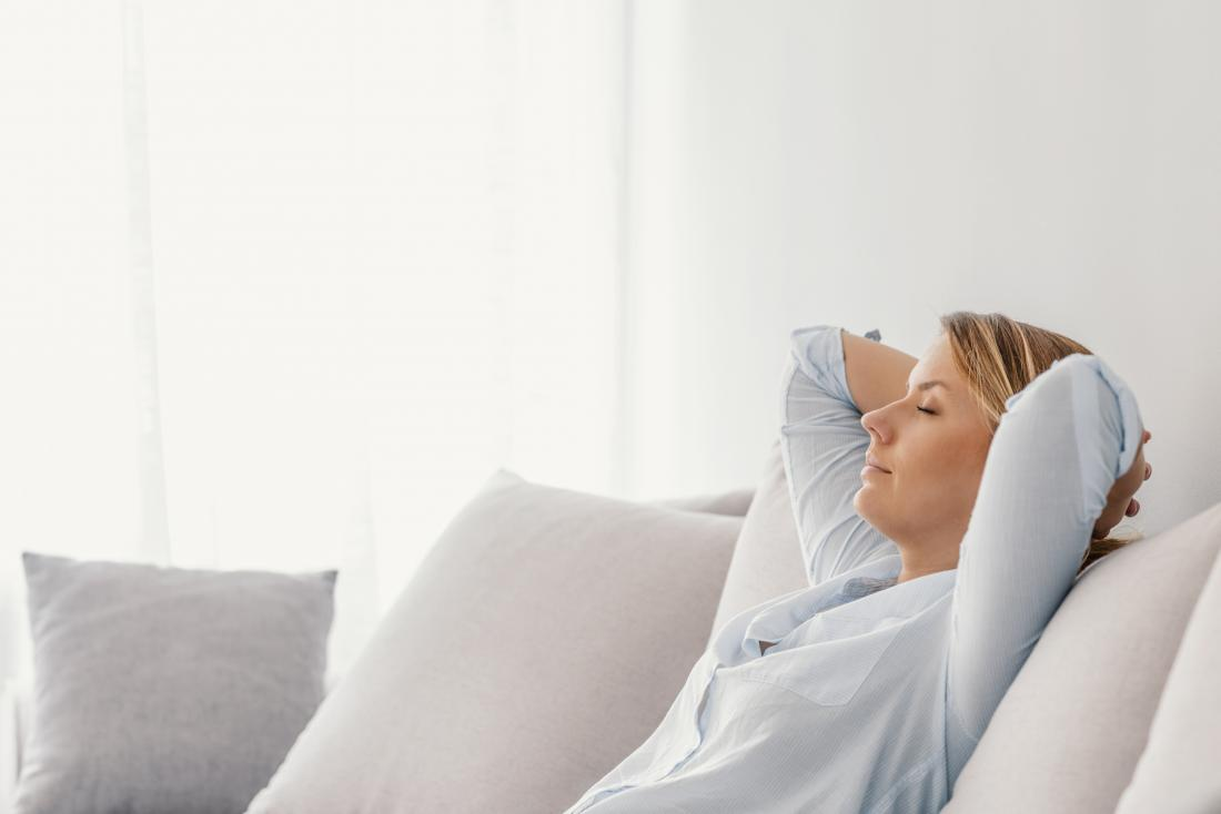 Woman doing breathing exercises on the sofa to improve lung capacity