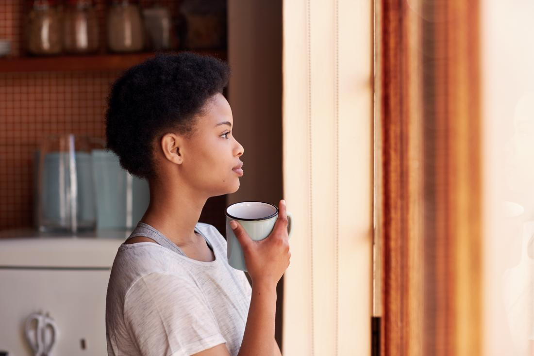 Woman with a mug looking out of window thoughtfully