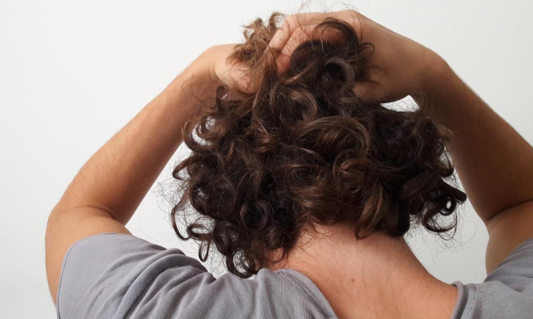 View of back of persons head as they hold their hair due to hair loss from diabetes.