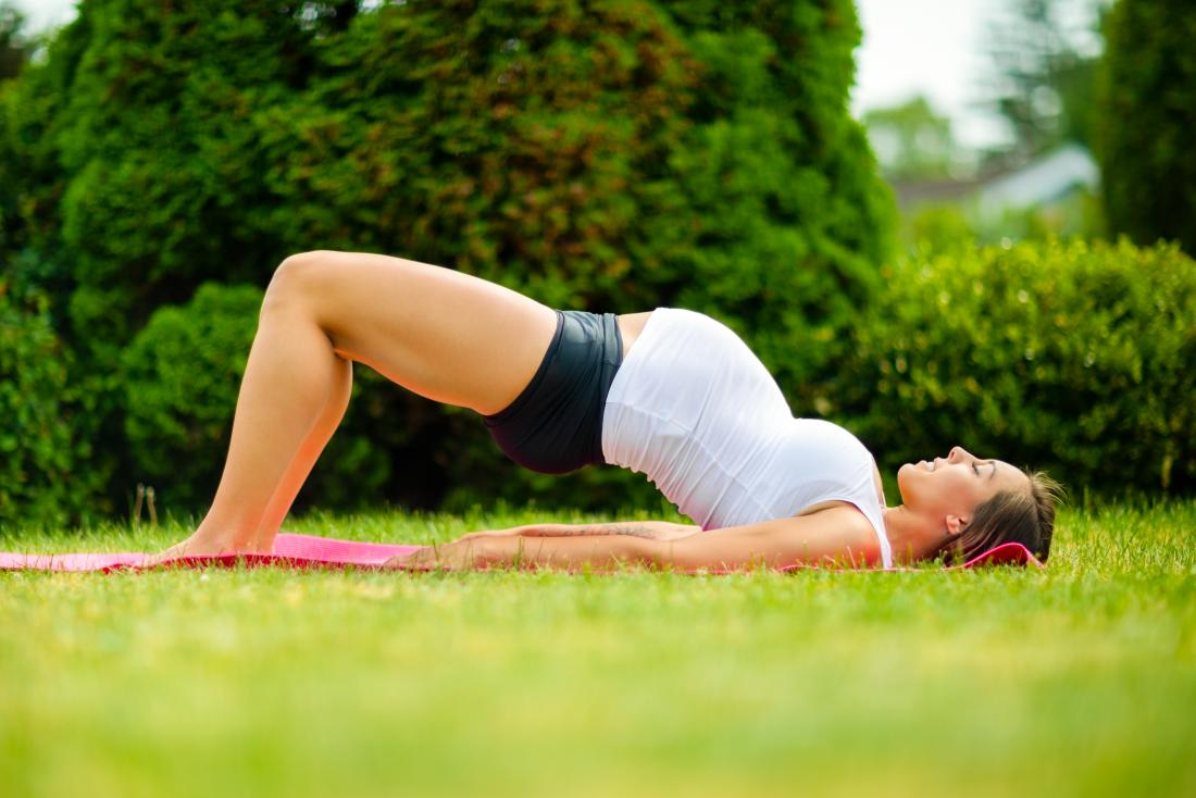 Pregnant woman performing bridge yoga pose stretch outdoors