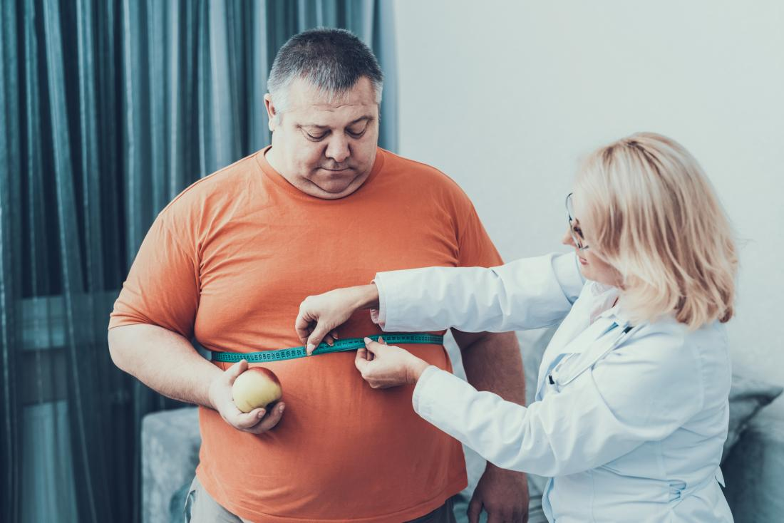 doctor taking measurements of obese man