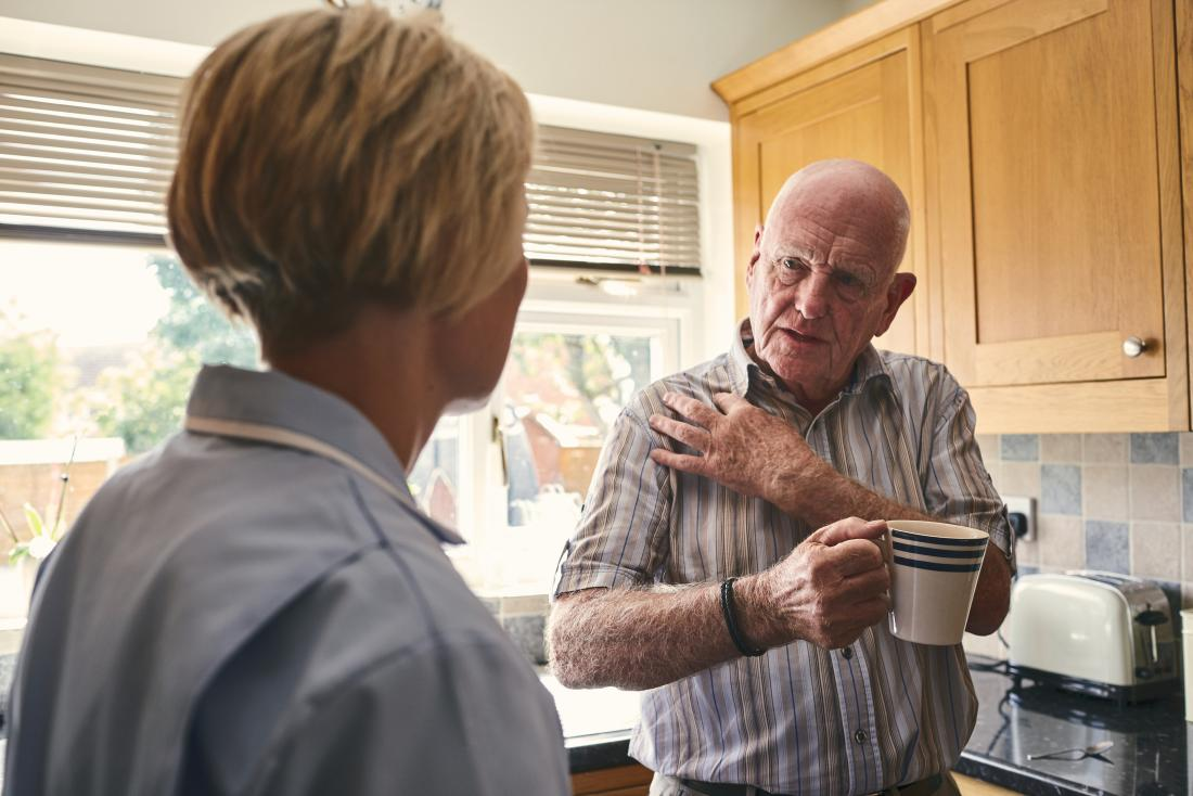 Senior man in kitchen holding shoulder because of pain showing home care nurse