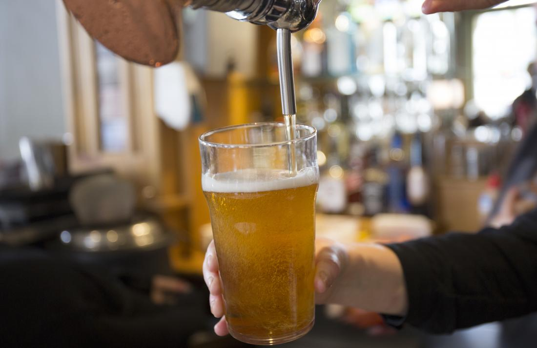 Person pouring beer from tap into beer glass