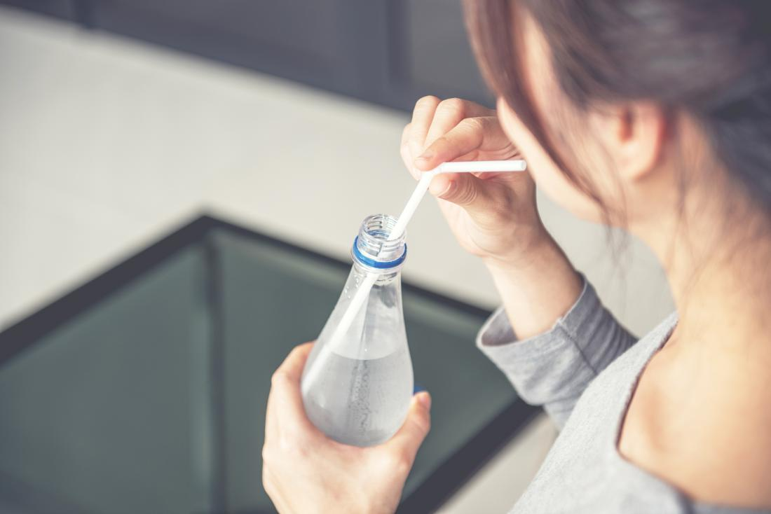 woman drinking water through a straw