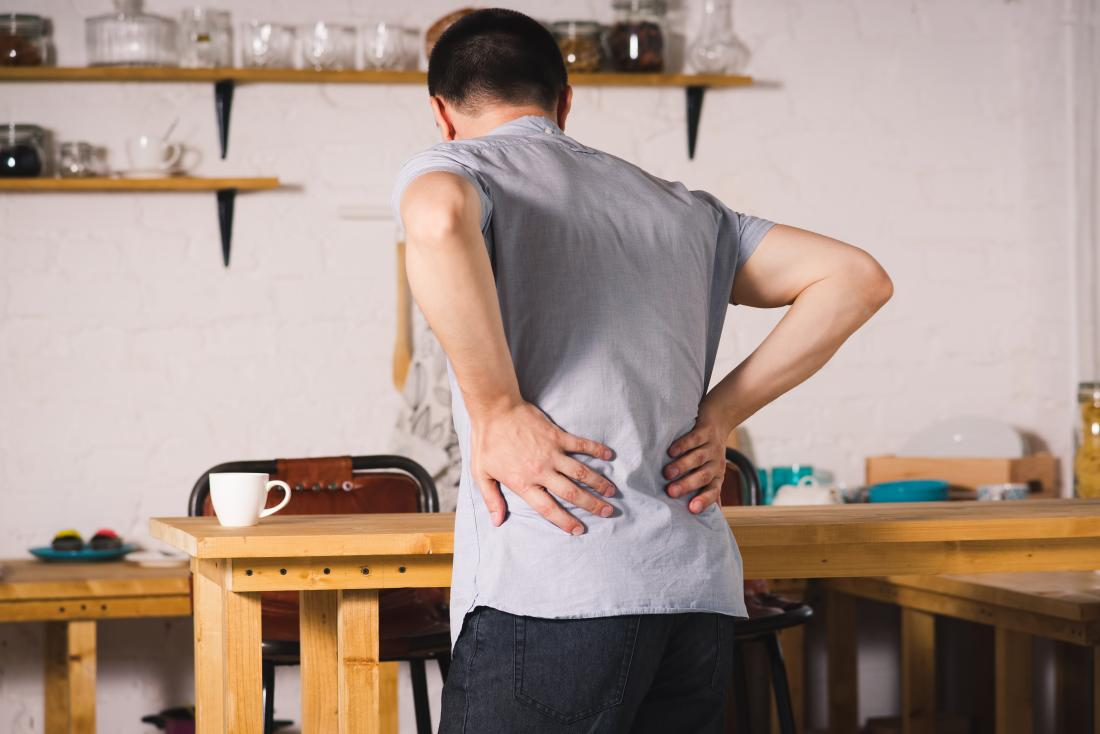 man in kitchen holding his lower back