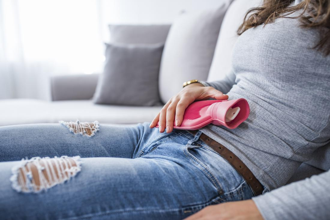 woman sitting on sofa holding small hot water bottle on her stomach