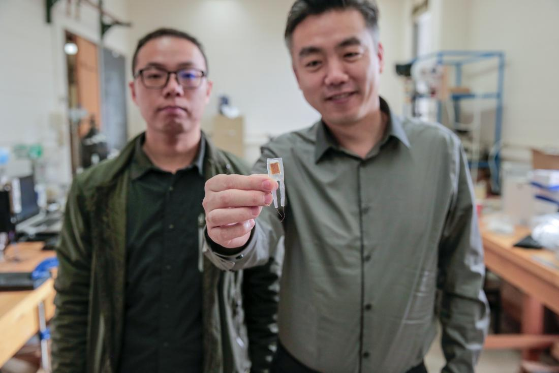 Graduate student Guang Yao (left) and Xudong Wang (right) hold a small implantable device. Image credit: Sam Million-Weaver