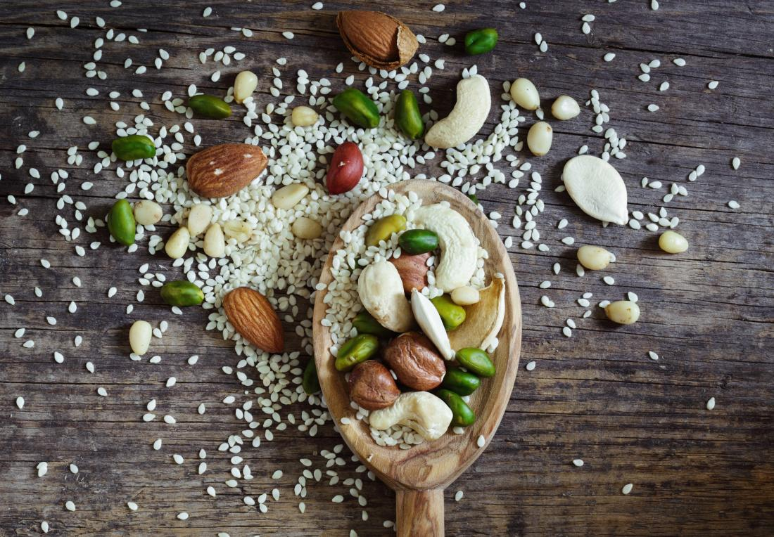Mixed nuts and seeds on wooden spoon over table, including pine nuts, almonds, pistachios, and cashews.