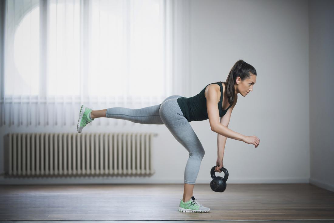 Mujer en el gimnasio realizando peso muerto de una pierna con peso