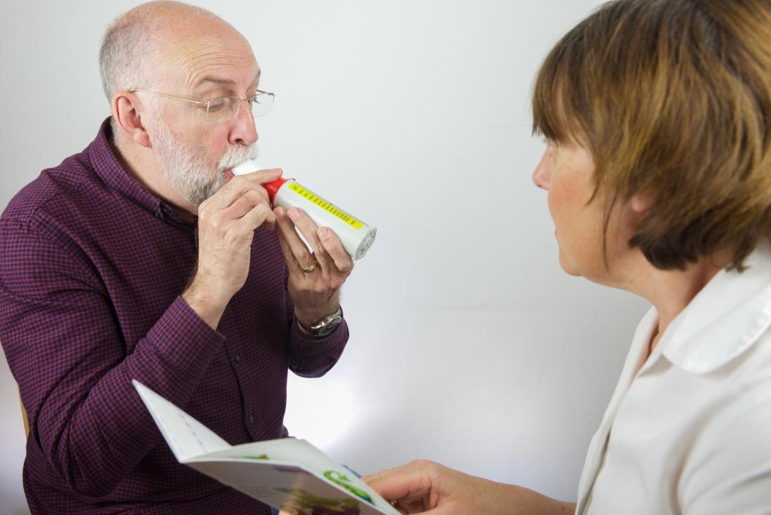 Man breathing into peak flow meter to test lung capacity as part of pulmonary function tests.