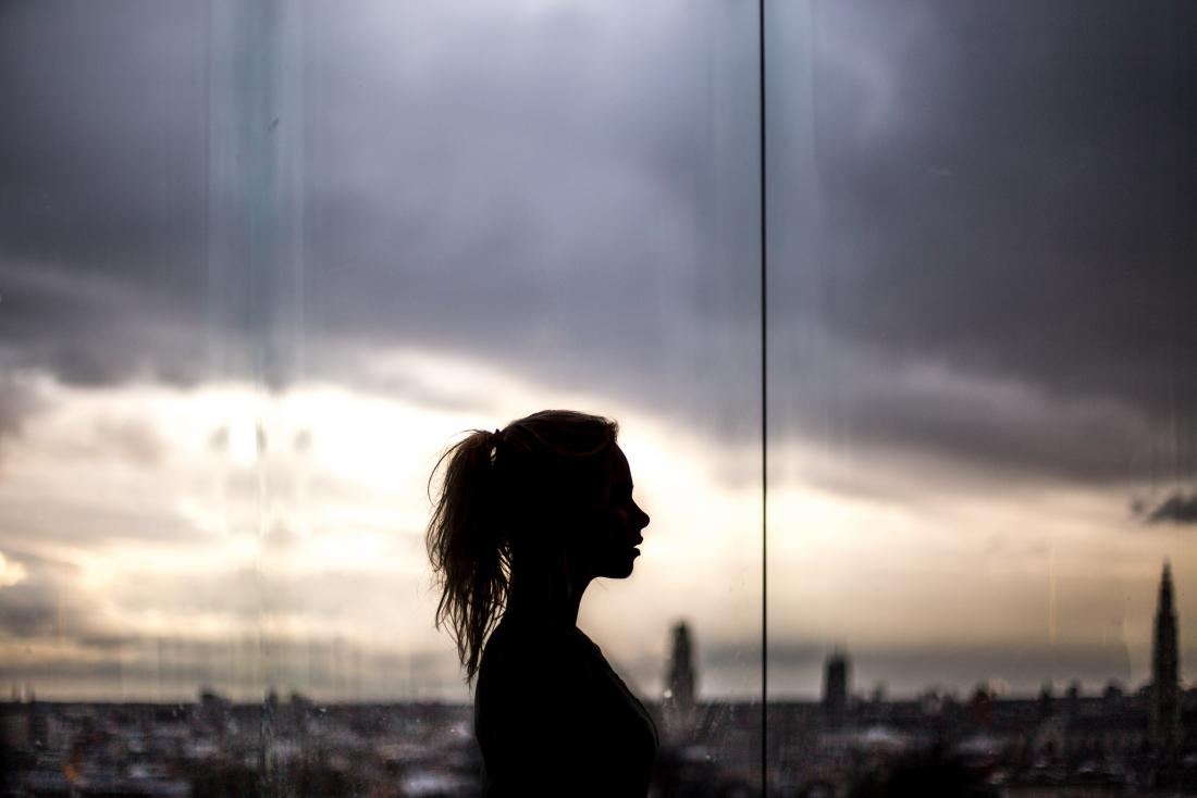 silhouette of a person against cityscape