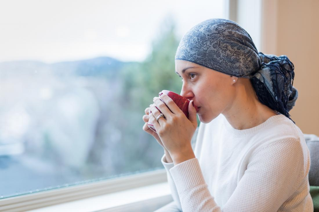 Cancer patient looking out of window drinking from mug