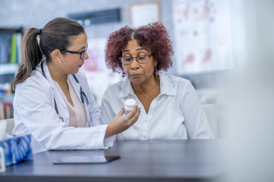 pharmacist showing drugs to patient