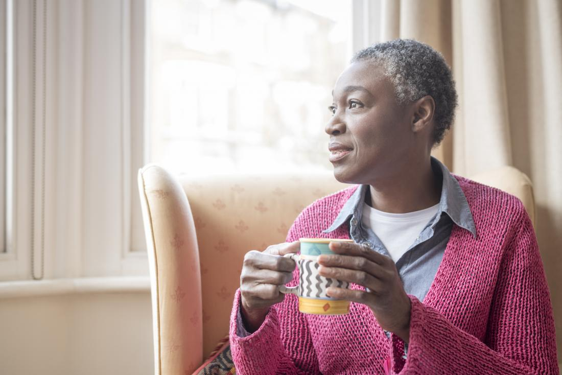 mature woman holding cup and looking out of window