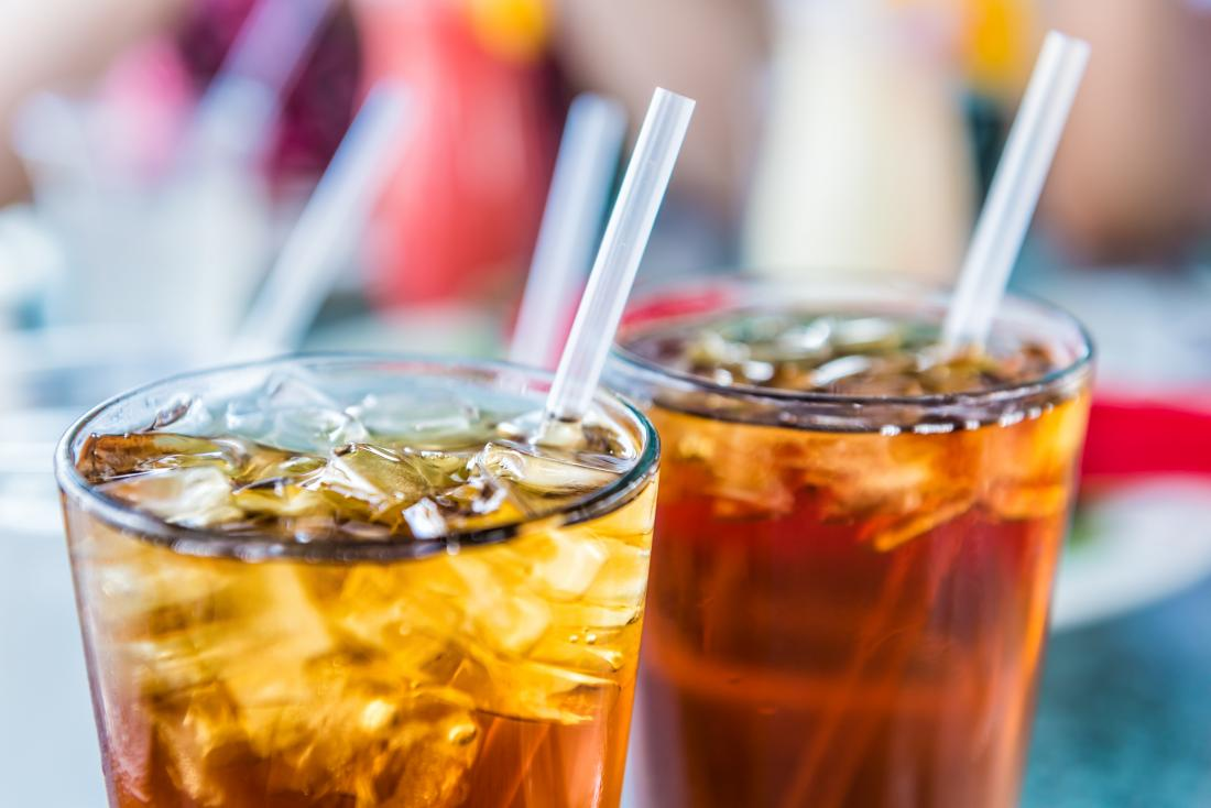 Drinks of ice tea or soda cola in glasses with straws