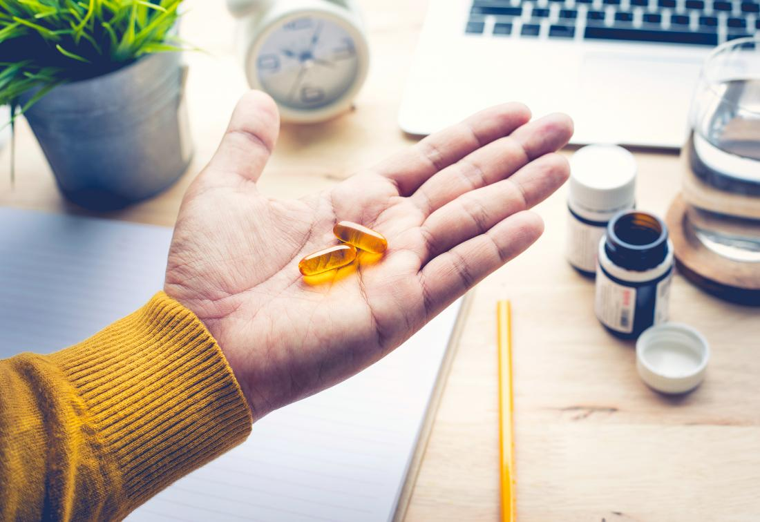 Person at desk holding omega-3 supplements in palm