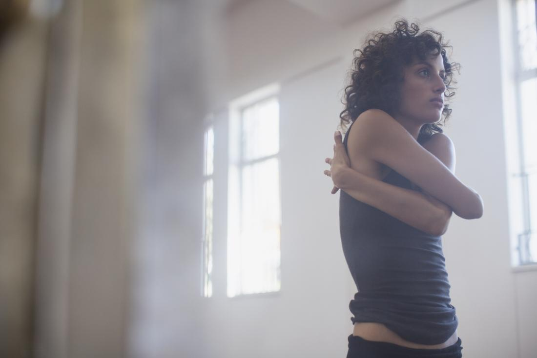 Woman hugging herself and stretching shoulder and neck.