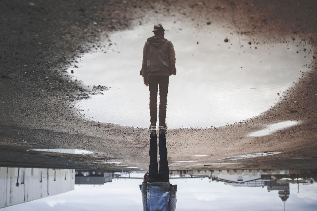 person reflected in a puddle