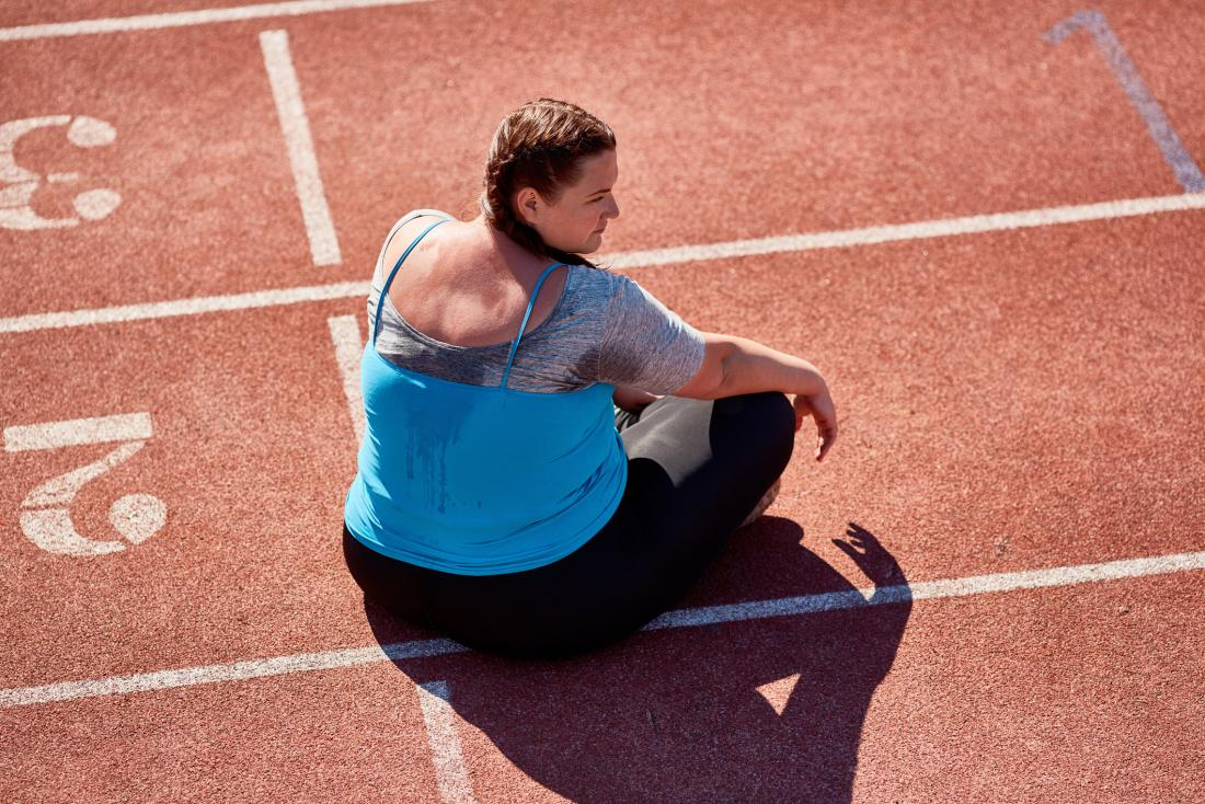 overweight woman looking discouraged on turf