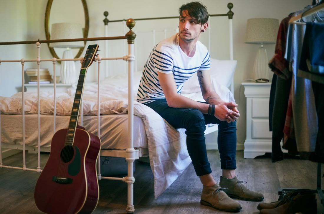 Man sitting on bed in bedroom with guitar and wardrobe