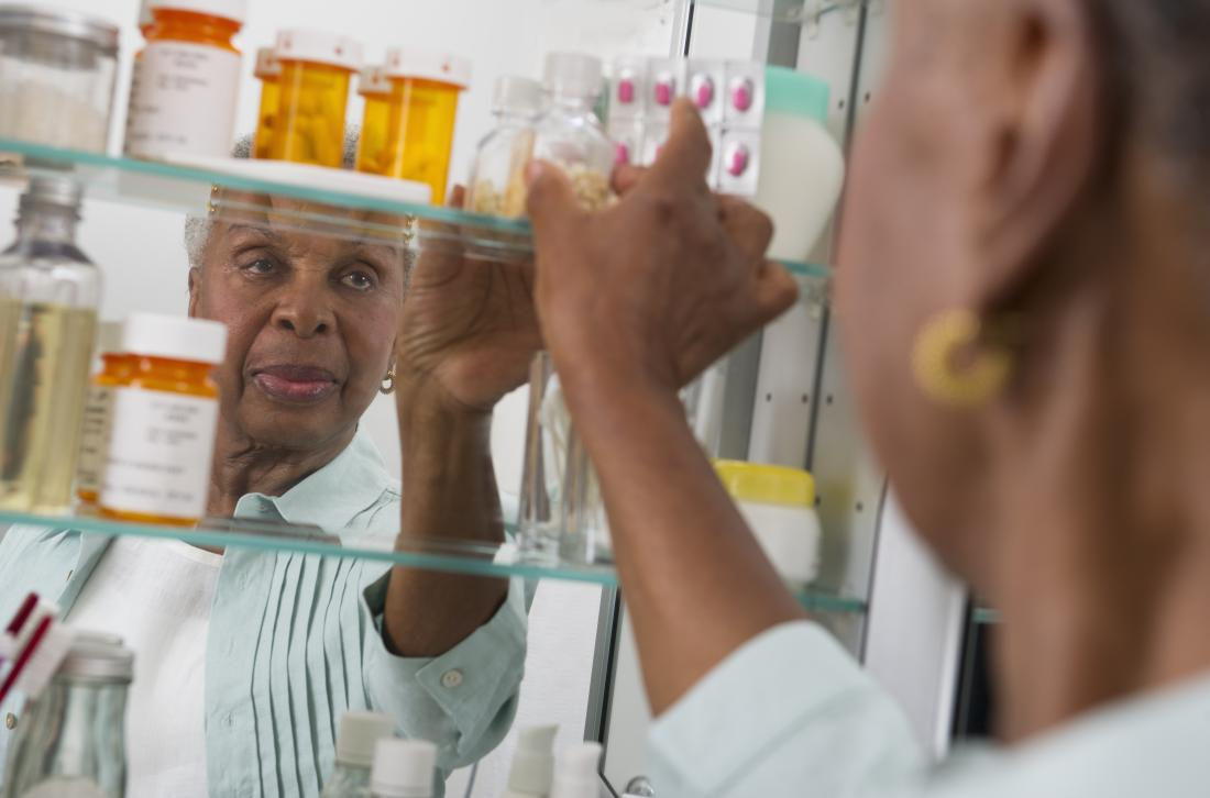 woman taking medicine from cabinet