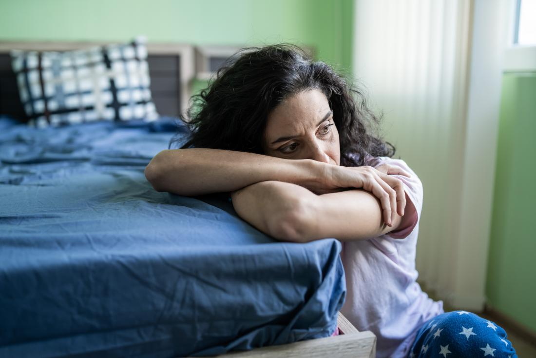 Woman sitting next to bed resting head on arms, suffering from insomnia and trouble sleeping, looking worried and stressed