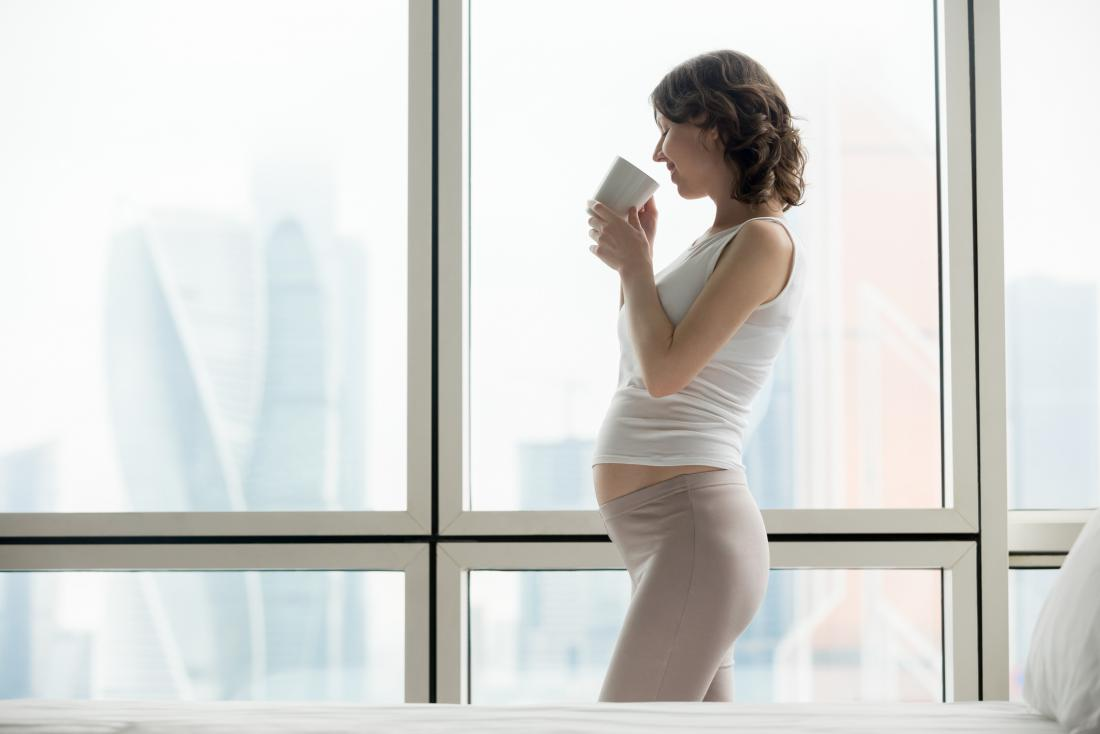 pregnant woman looking out of windows