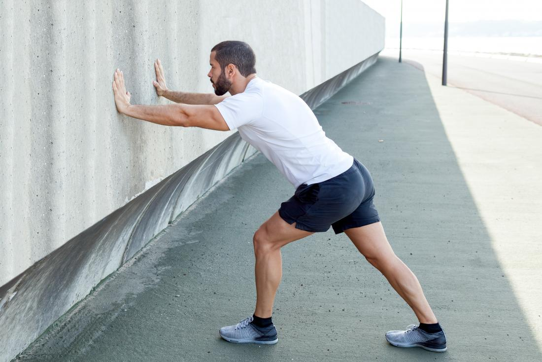 Man doing calf muscle and foot stretch against wall